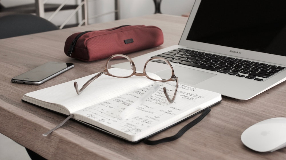 eye glasses on a desk in front of a computer